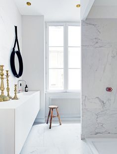 House tour: a modern French apartment within an opulent 19th-century shell: An 'Adnet Circulaire' mirror from Gubi hangs above a Boffi vanity in the bathroom. The stool is 19th-century Chinese.