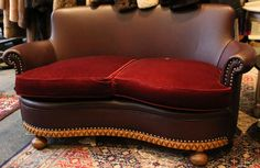 A 1920s / 30s oak decorated twin seat curved sofa, turned legs, contemporary burgundy leather upholstery. #retail