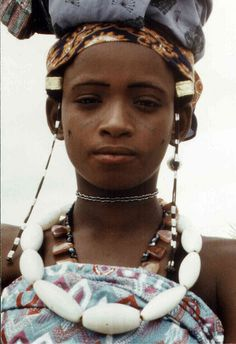 This photo by Flickr user (Dogan56) entitled Ragazza Fulani, Nigeria is one of the few pictures that I have found that shows so beautifully an example of old Venetian 'Agate' glass beads from the African Trade.  Venetians made these large glass beads to trade with the Yoruba.  They're milky white, semi-translucent with veins & look like stone.  If by chance they were stone, they would be white Indian Agate beads, which would also have come to Africa through the trade routes.
