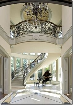 Too many things I love in this photo: winding staircase, huge windows, white, a grand piano. Usually not into grand entrances but this one's an exception.