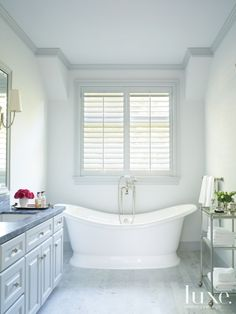 the elegant master bathroom includes carrara marble tile flooring from materials marketing and countertops from walker zanger