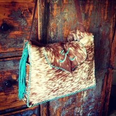 A new twist on the Buckaroo Diaper Tote.  This customer asked for a long cross body shoulder strap with turquoise fringe and stones, and a large flap closure with her initial in turquoise suede. Custom purses, bags and totes from gowestdesigns.us