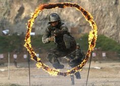 A member of People's Liberation Army (PLA) coastal defence force jumps through a burning obstacle during a drill to mark the 87th Army Day at a military base in Qingdao, Shandong province July 29, 2014. The PLA Army Day falls on August 1 every year. Chinese President Xi Jinping has pledged to strike hard against graft in the military, urging soldiers to banish corrupt practices and ensure their loyalty to . Picture taken July 29, 2014. REUTERS/Stringer