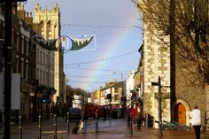 A November Rainbow over Dover High Street, Kent, England, UK. Late autumn rain and sunshine view from Biggin Street shopping precinct to the Eagle Inn (white building beneath the rainbow). The 80-foot high tower on the left belongs to the Victorian Church of St Columba (St Martin's Court) scene of a 2007 fire. Note the cannons at the base of the Town Hall on the right (Tourist Information Office nearby). An Urban Dover Architecture and History photo. See…