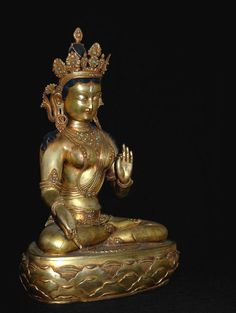 A Nepalese seated White Tara statue. This 20th century statue of the goddess Tara is cast in bronze and gold gilt, with intricate gemstone inlay.
