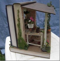 """Shannon Moore's """"Potting shed,"""" sideview, made from three books. More of Moore's book art is at the link, """"Books in the hands of Shannon Moore"""" at Book Patrol. Book Crafts, Diy And Crafts, Paper Crafts, Altered Books, Altered Art, Book Sculpture, Fairy Doors, Book Folding, Book Projects"""