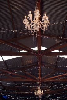 Tin roof barn wedding lights ~ chandelier and fairy light strands strung through the beams. Barn Wedding Lighting, Barn Wedding Decorations, Wedding Reception Venues, Barn Lighting, Lighting Design, Shed Wedding, Wedding 2017, Wedding Gowns, Gold Bridesmaid Gowns