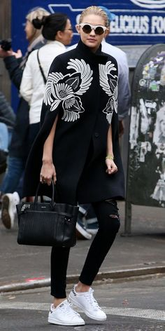 Gigi Hadid goes all black and white in an embroidered cape, ripped jeans and Adidas sneakers