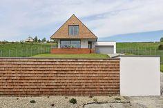 Martin a Baška sa neobávali pokryť strechu tradičným  šindľom. Je z kvalitného dreva, štiepaný v prirodzenom  smere vlákien, takže štruktúra dreva zostáva  nezmenená. Vďaka tomu menej absorbuje vlhkosť  a podlieha zmenám ako rezaný šindeľ.  Strecha poriadne presahuje obvodové múry a spolu  s rozšíreným základom a zábradlím dookola vytvára  priestor pripomínajúci tradičnú verandu.