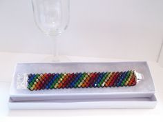 $40 on Etsy: These Beaded Rainbow Crystal bracelets were hand beaded by me with genuine swarovski crystals on a Jet colored, netted background. The closure is a silver plated box clasp. My bracelets are made to order and are reinforced carefully for even the most strenuous of wear. This bracelet is approximately 1 Inche/ 25 millimeters wide. Rainbow Crystal Bracelet , Silver Plated , Box Clasp , Floral Pattern , Equality Jewelry , Genuine Crystal , Custom Fit , Elegant Design