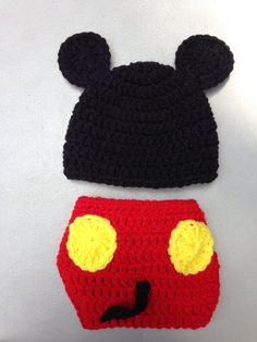 Adorable crocheted Mickey Mouse ear hat with diaper cover! Hat is black with big mouse ears. Red diaper cover has two yellow buttons and an adorable mouse tail on the backside. Button enclosure on the front. Button allows for adjustable sizing. Hat is standard newborn size (12-14 inches)