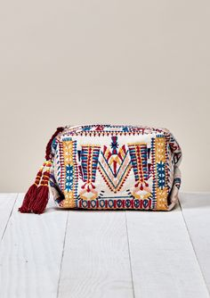 Intricately embroidered, compact, pinched cube makeup bag features a zippered closure and beaded tassel detail. Self: 100% Cotton, Lining: 100% Polyester Size: W: 8in x H: 3.5in Style: DR-2115