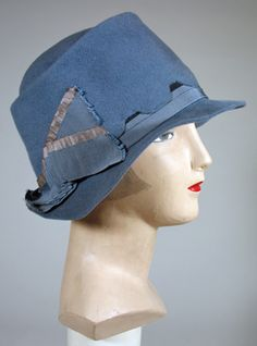 Circa 1928 blue felt cloche has a wonderful scalloped crown set over a grosgrain ribbon band with a pleated taupe and blue ribbon cockade. The brim is narrow while the top of the square edged crown is telescoped. This cloche shows the harder edges, more tubular line of the later 1920s. Lined in black.