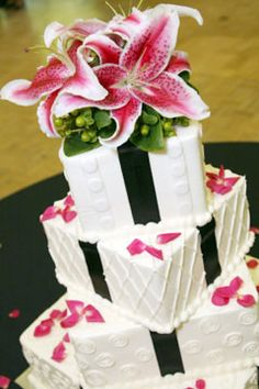 Four tier white wedding cake with fresh stargazer lilies as a wedding cake topper.