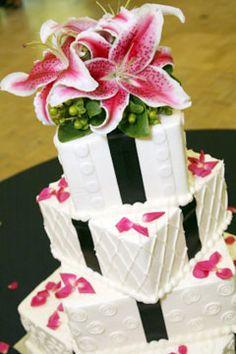 Four tier white wedding cake with fresh stargazer lilies as a wedding cake topper.