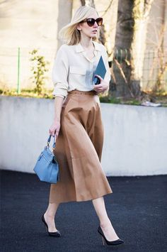 Jane Keltner de Valle wears a button-down blouse tucked into a leather midi skirt with black pumps and a pastel blue satchel