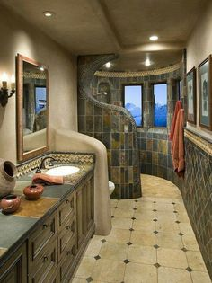 Dark multi-slate on walls, light travertine floors (or marble), rustic cabinets.