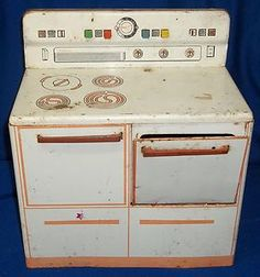 Toy tin stove with plastic push buttons - early 1950s  (My cousin Carol had this and I was SO jealous of those colorful pushbuttons on the back!)