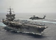 A helicopter flies past the aircraft carrier USS Enterprise.
