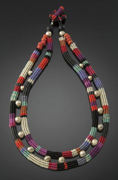 Silver, Red and Jewel Tones Echo Necklace by Julie Powell. Tiny glass seed beads, Vintage European, from Czech Republic and Japan- handwoven, bead by bead with a needle and fishing line. Worked in the round, flexible tubular formation in Herringbone stitch, then stuffed with glass beads for stability. Accented with silver and Czech glass. Hand woven toggle and clasp. Limited edition of 25.