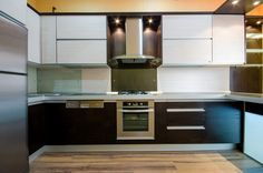This U-shaped kitchen has dark wood lower cabinets that contrast beautifully with the light wall cabinets and a glass backsplash by the sink.