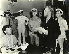 Surrounded by American naval officers, a U-boat commander translates instructions to his crewmen in the shadow of the brig that will soon be his home. His submarine had fallen victim to the US Coast Guard cutter Icarus.