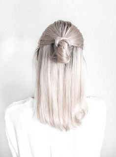 A White Hair Color Ideas which has been Gently Pulled Back into a COOL Top Knot