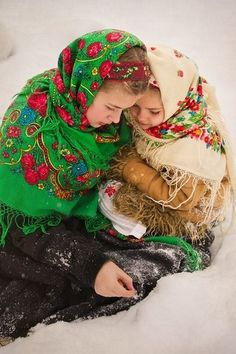 Two girls dressed in Russian Pavlovsky Posad shawls are playing in the snow. The colors are so beautiful.