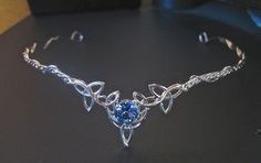 A Celtic forged and fashioned Trinity Knot Headpiece featuring a 10mm round Blue Topaz gemstone.