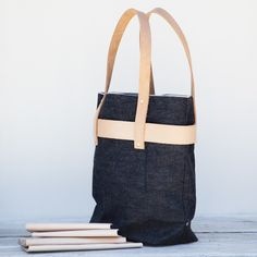 Artist : Roberta Rennie  A sharp update on the traditional tote, with a tall silhouetteconstructed  of 100% cotton selvedge denim. Features vegetable-tanned leather banding  detail andlong straps to fit perfectly over the shoulder.  Available only at YONDER  Dimensions: Denim bag is 15&quo