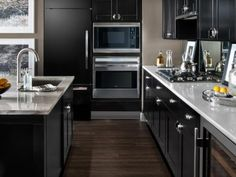 (Thumbnail size) Appliances : Gray Modern Kitchen With Black Cabinets. black kitchen appliances. black refrigerator. stainless steel microwave oven. stainless steel oven. black kitchen cabinet. white kitchen island. granite countertop.