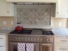 Granada stone and glass mosaic picture above the stove top - very elegant, but I wish they had committed to the rest of the splash too!