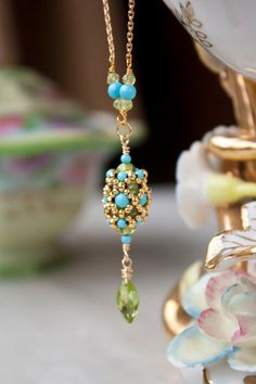 Beautifully smooth turquoise and peridot encased in gold plated seed beads dangle from a gold filled chain. Finished with a faceted marquis shaped