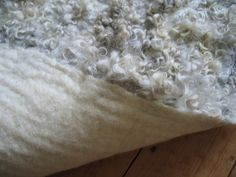 Tutorial hand felted fleece rug - use squishiest types of fiber for under padding. Gotland fleece curls on top-put down curls first-add carded wools next and felt.