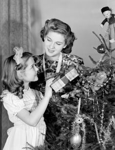 Woman and young girl by a Christmas tree c 1950.
