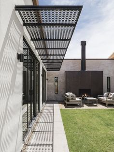 Modern home with outdoor, desert, and grass. Custom cut steel awning. The awning design uses the archetypal gable shape of the house and rotates it to create the perforated pattern Photo 5 of Canal House