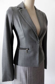 """Review-Jacket-Size-6-8-or-US-2-4-Grey This stylish jacket from Review is timeless.  It is tailored with a one button front closing.  It is grey with a wide black panel running along the length of the inside of the sleeves and down the side to the bottom of the hem.  The cuffs have 14cm (5.5"""") exposed zips.  The same zips are on the two faux front pockets.  The shoulders have light padding. It is fully lined in pink satin.  There is a rear vent for extra comfort."""