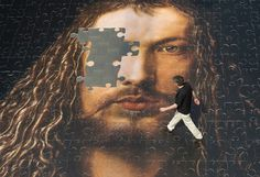 A man walks on a giant jigsaw showing an Albrecht Duerer painting ´Self-portrait in fur coat´ in Nuremberg, Germany. The jigsaw, made of 1023 parts on 300 square meters, is supposed to be built by citizens at the red square in Moscow to open the German year in Russia.