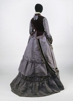 "Grey silk taffeta and velvet ensemble (back view), 1868-70. Ensemble consisting of a bodice, skirt and sleeveless jacket. Said to have been worn by a ""city merchant's wife""."