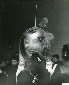 A woman in a space helmet smoking a cigarette, 1950. Photo by Weegee (Arthur Fellig, 1899 - 1968).