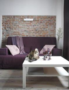 canapé pourpre devant le mur en brique rustique dans le salon