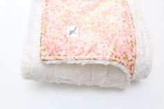 "This is the most luxurious and soft baby blanket in the history of blankets! The gorgeous faux fur is an off white and so unbelievably soft to the touch absolutely perfect for our sensitive little ones. The blanket measures a generous 35"" x 43"". The gorgeous pink print has a beautiful metallic gold confetti all over and as you can see from the photos it is so beautiful. This blanket is also three layers thick for extra coziness! They are also sewn with the most gorgeous m..."