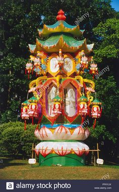 Singapore, huge Chinese lantern, brightly coloured structure, small lanterns hanging from top, panel of gold Chinese script, grass and trees in background. Stock Photo