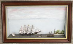 """HIP DIORAMA. Absolutely delightful 19th century American sailor folk art diorama depicting a charming coastal scene with 3 sailing ships and a tugboat. The foremost vessel is a 4-masted American bark identified on the starboard trail board and the mizzen pennant as the """"DIRIGO."""" She is depicted under full billowing sail, all of which are made from carved wood! She is outfitted with a carved wooden female figurehead, a capstan on the focs'le, anchor on the cat, 2 deck houses, a lifeboat ..."""