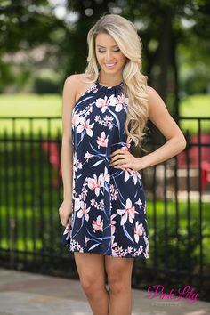 We adore this vibrant halter top dress! Featuring a bold floral print in white, peach, yelllow, red, and blue on navy fabric, this print will shine in a crowd! It also features an adjustable halter tie creating a fabric bow in back, an open back, and elastic around the back.