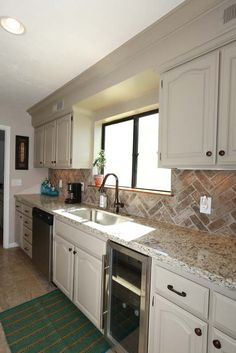 Raised ceilings, herringbone brick backsplash, new beverage fridge, neutral color cabinets, bronze hardware & fixtures. It all blends seamlessly with most decors!
