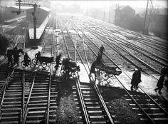Overstekende voetgangers, enkele handkarren en een bakfiets op de spoorwegovergang in de Vleutenseweg, gezien vanaf de voetbrug. Links op de achtergrond het Buurtstation en het emplacement van het Centraal Station. Catalogusnummer  816503