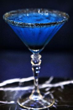 Witches Brew – Bacardi Dragon berry rum, Blue Curacao, Creme de banana, fresh squeezed lime juice, served up in a martini glass rimmed with black sugar. Via