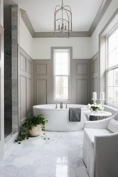 An Arch Top Lantern illuminates an elegant white and gray master bathroom equipped with an oval freestanding bathtub placed on large marble hex floor tiles beneath a window partially framed by dark gray wainscoting. Bathroom Floor Tiles, Bathroom Colors, Bathroom Wall, Small Bathroom, Bathroom Ideas, Master Bathrooms, Remodel Bathroom, Bathroom Cabinets, Bathroom Storage
