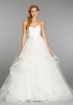 Ivory strapless natural waist bridal ball gown with silk radzmir crossover bodice, full tulle skirt with horsehair flounces and chapel train. Shown with matching horsehair veil.